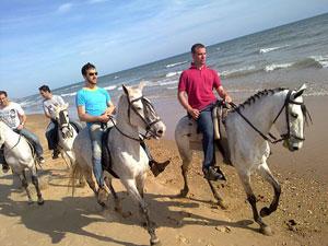 Los protagonistas chapotean con sus caballos por la orilla