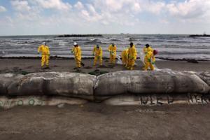 Unos operarios limpian una playa del vertido de crudo