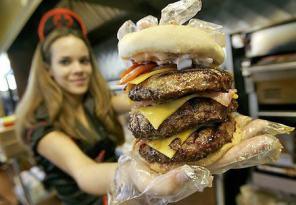 Una camarera muestra orgullosa una hamburguesa gigante