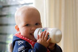 Un pequeño bebé sonríe biberón en mano