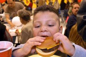 Un niño disfruta comiendo una hamburguesa